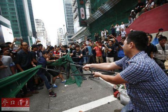 """香港反""""占中""""民众(右)试图移走""""占中""""参与者设置的路障。"""