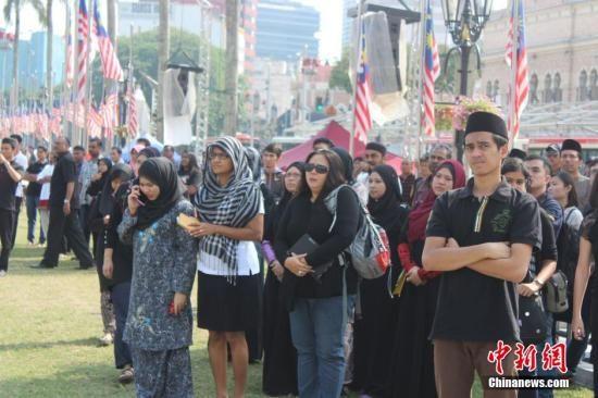 马来西亚首批MH17罹难者遗体8月22日运回吉隆坡,马来西亚政府将22日定为全国哀悼日。图为民众自发前往吉隆坡独立广场向罹难者致哀。中新社发 赵胜玉 摄