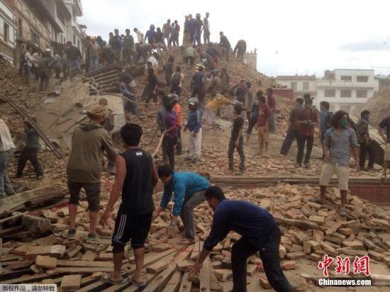 当地时间2015年4月25日,尼泊尔加德满都,震后倒塌的建筑旁志愿者帮助救援。当天,尼泊尔发生8.1级地震,首都加德满都震感强烈,有多栋房屋倒塌。
