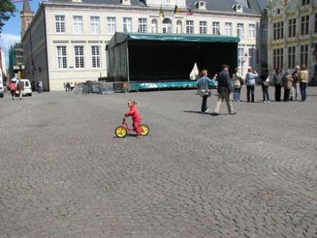 比利时古城布鲁日的老广场上一个正在骑车的女孩
