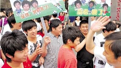 人大附中的12名小足球队员在走出考场时受到了如明星般的欢迎,教练及老师们粉丝一样,打出像追星的牌子来欢迎孩子高考结束。本报记者 胡雪柏 摄