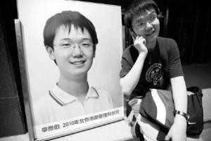 6月23日,人大附中将李泰伯的巨幅海报照片摆放在教学楼前以示庆贺,而他则在照片旁边面带笑容打电话