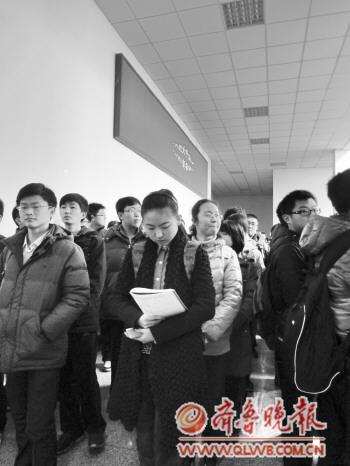12日下午1点,最后一组考生排队等候进入考场。一位考生趁等候时间复习。