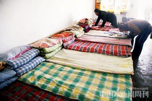 在教鹏焉小学宿舍内,领孩子来报到的家长给孩子整理床铺。摄影/ 韦亮