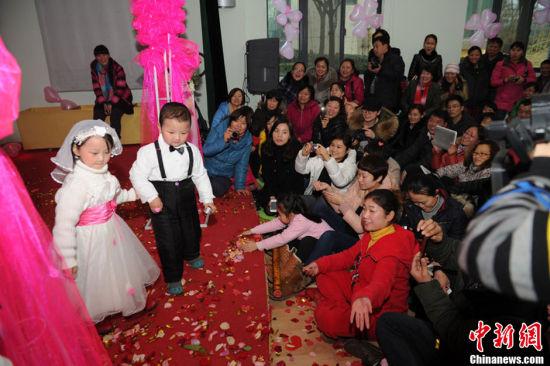 """1月11日,河南郑州一家幼儿园为100多名""""自由恋爱""""的孩子举办了一场""""集体婚礼""""。小""""新郎""""和小""""新娘""""的家长们也在婚礼现场见证。张翼飞 摄 图片来源:CFP视觉中国 1"""