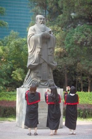 """中国人民大学几名毕业生在离校前""""拜别""""孔子像。新京报记者 薛�B 摄"""