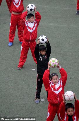 河南一小学普及校园足球 学生抱着足球跳操