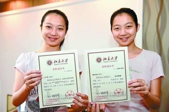 7月29日,在安徽省合肥市瑶海区,双胞胎姐妹徐安如(右)、王安意在家中展示她们收到的北京大学录取通知书。解琛/摄
