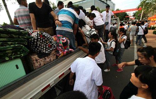 新生报到行李堆满路边 校方出动大卡车运送