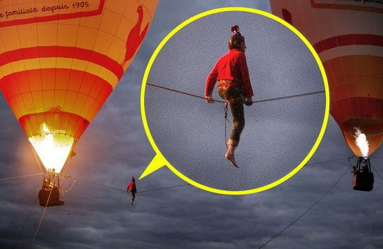 米洛特正在两个热气球之间的钢丝上休息。摄影师乔夫尔拍摄到整个表演过程。(网页截图)