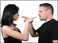 Two people pointing at each other