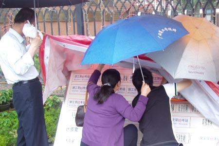 6月6日高考现场传真:一家人在雨中看考场