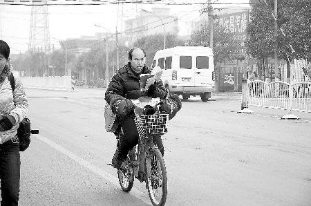 男子边骑电动车边看玄幻小说