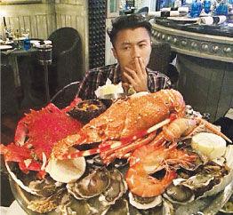 谢霆锋面对一大堆鲜美的海鲜大快朵颐。