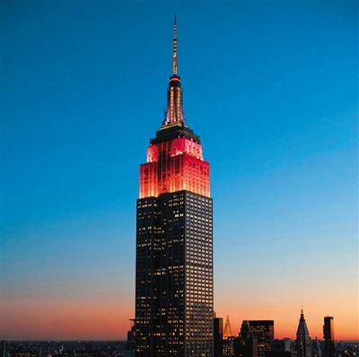 当地时间29日,纽约帝国大厦点亮红黄彩灯。