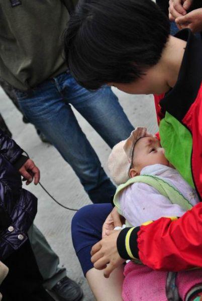 志愿者为失去父母的孩子喂奶
