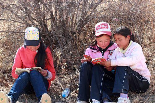 拿着捐赠书籍开心地坐在山上阅读