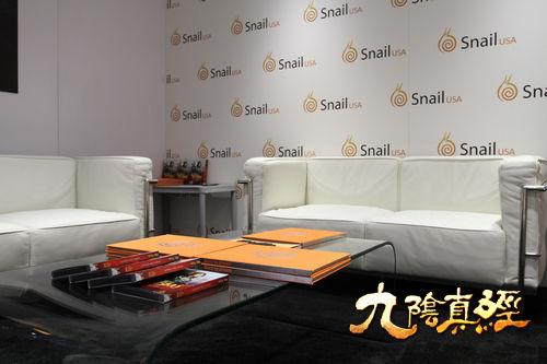 E3展区一角,桌上堆叠着九阴实体版客户端
