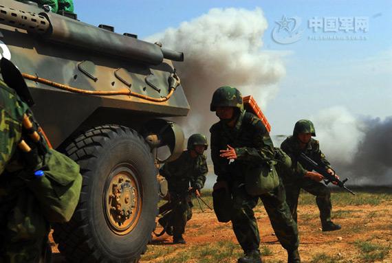 资料图:解放军举行演习,士兵从轮式战车下车后迅速展开突击