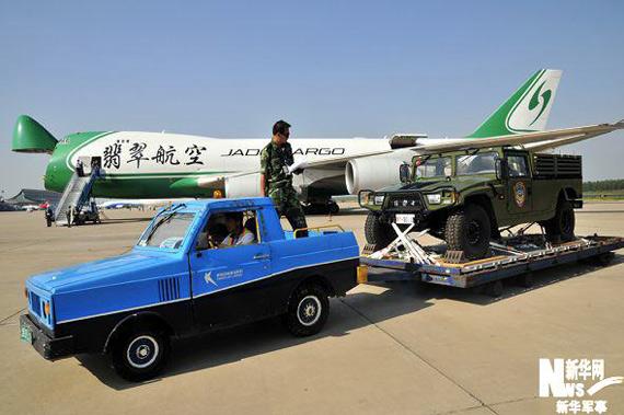 """机场工作人员正在装运""""跨越-2009・青铜峡""""首批远程投送空运梯队车辆。新华军事高航摄"""