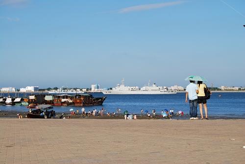 资料图:游人休闲区域能看到解放军海军战舰