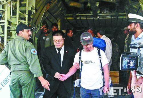 6月23日,幸运逃生的中国登山者张京川(左三)走下军用飞机供图/IC