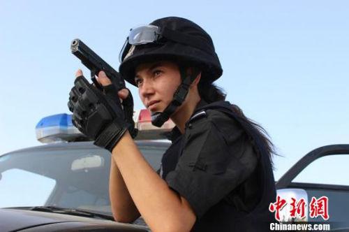 资料图:新疆麦盖提县27岁的维吾尔族姑娘米日办・买买提明曾多次荣获模特比赛冠亚军,但她在成名之后考取了麦盖提县公安局一名特警。 张胜开 摄