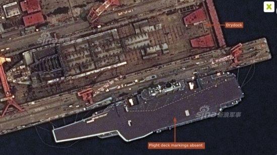 """资料图:美国""""数字地球""""商业卫星日前公布了今年7月份在大连船厂上空拍到的,中国海军航母辽宁舰维护照片。图中辽宁舰停在码头正在进行甲板重新划线工作。辽宁舰于今年4月份回到位于大连的船厂进行中期维护。9月份,辽宁舰完成维护工作离开大连港返回母港。"""