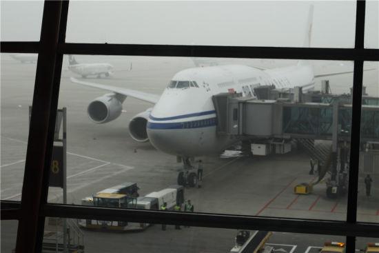 候机厅玻璃后的747-8,雾气虽重难掩芳华