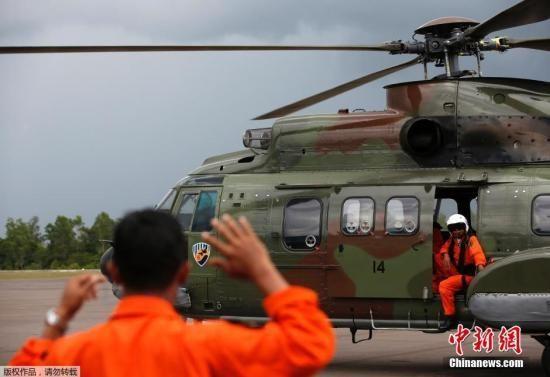 当地时间2015年1月4日,印度尼西亚庞卡兰布翁,印尼空军在暴雨中登机,前往搜寻亚航QZ8501航班遇难者遗体
