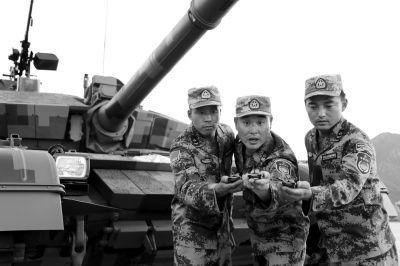 坦克方队驾驶员丁辉(中间)与战友们交流训练方法。