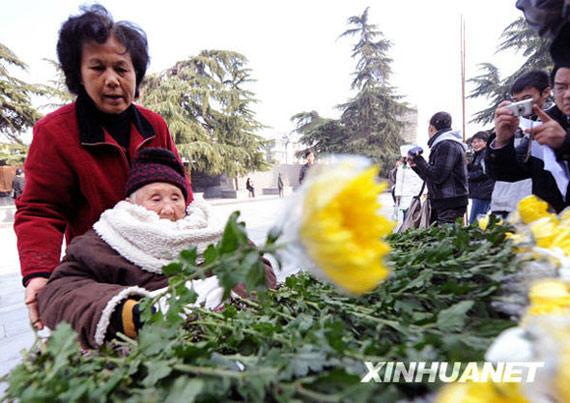 12月13日,武警战士在悼念仪式上为遇难者敬献花