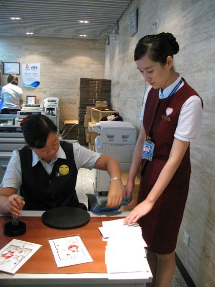 国航地服人员特意到T3航站楼邮局盖上8月8日当天的邮戳。(朱梅摄)