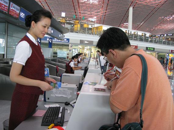 旅客认真填写名信片,生怕自己收不到这份特殊的祝福。(朱梅 摄)