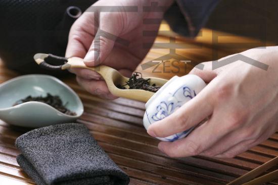 用茶则从茶叶罐中舀取茶叶