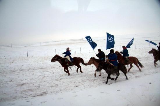 热情的欢迎马队,手擎奔驰旗帜飞奔在雪原夹道欢迎
