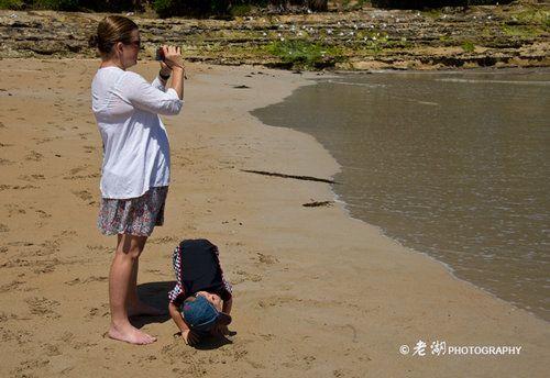 海滩上陪伴孩子们嬉戏的母亲