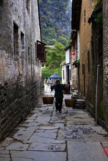 行走在小巷中的挑夫