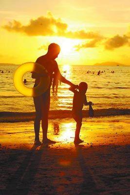 11月20日,一场冬雨过后,海南三亚地区天气晴好,气温达到30摄氏度,众多游客来到海边纳凉、游玩,感受美丽夕阳下的冬日浪漫时光。CFP供图