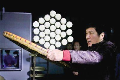 在衢州,看徐成正师傅为胡麻饼上麻,就像观看一场杂技。随着他猛地一震大箩,30个小饼保持着规则的六边形一起腾空而起,就像一队听从指挥的士兵。