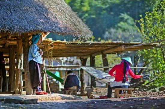 在翁丁迄今还保持着男耕女织的传统,寨子里的妇女一般空闲的时候都会在自己家门口拉起纱线就地织起布来。