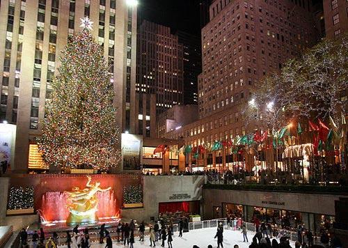 12月7日,一些游客在美国纽约洛克菲勒中心前巨大的圣诞树下溜冰