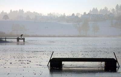 4、1月13日,瑞士苏黎世,一名男子察看部分冰封的湖面。
