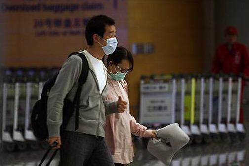 4月27日,两名从上海浦东国际机场入境的旅客,戴着口罩通过安检通道。 图:记者赵昀/《东方早报》