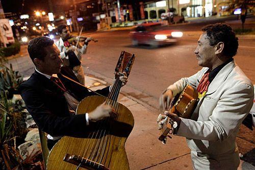 """""""流浪者乐队""""的成员们在路边弹唱,等待顾客光临"""