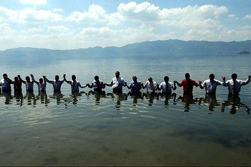 教堂的成员们在圣萨尔瓦多附近的湖中一起为进行洗礼的人祈祷
