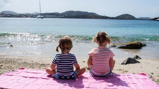 两个女儿坐在沙滩上萌萌哒。
