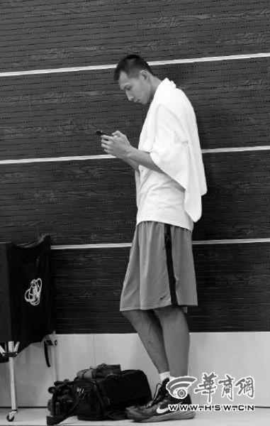 参加测试前,易建联悠闲地站在场边看手机 华商报记者 闫文青/摄