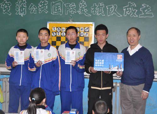 获佳绩棋手与年级组长李老师接受奖品并合影