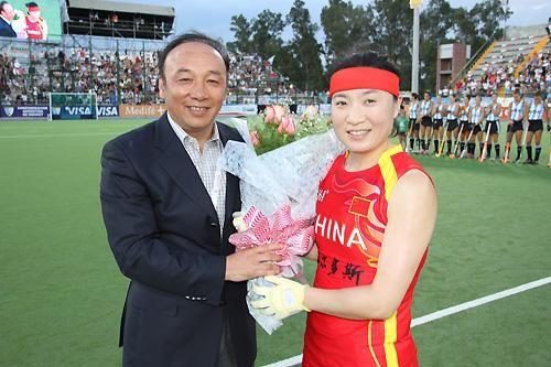 中国曲棍球协会主席雷军向唐春玲献花表示祝贺(图片提供:中国女曲领队 张萱)